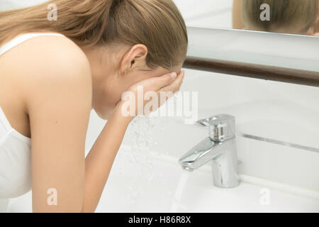 Young female washing her face with tap clear water near the sink - Stock Photo