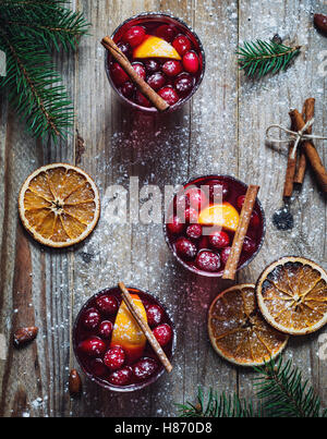 Hot spicy mulled wine with cranberries, cinnamon and orange in glasses on wooden table. Top view - Stock Photo