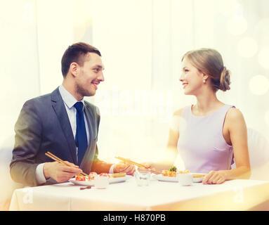 smiling couple eating sushi at restaurant - Stock Photo