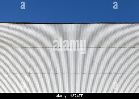 Industrial building wall made of corrugated metal sheet, under blue sky - Stock Photo