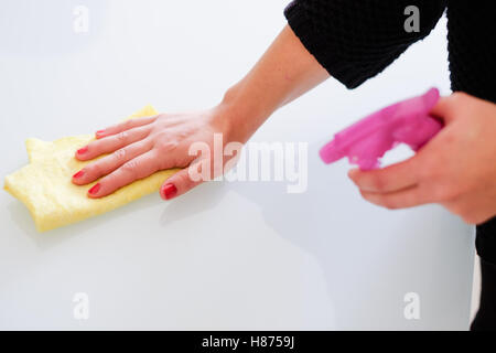Woman cleaning white surface in  the kitchen at home - Stock Photo
