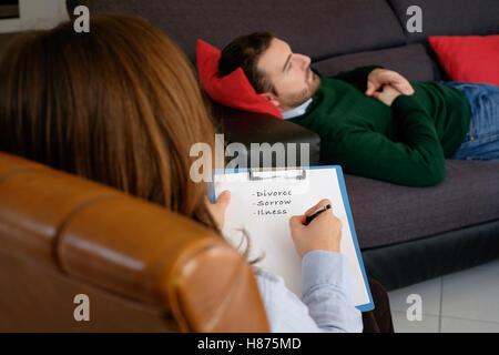 Man with mental health problem in the psychiatrist studio - Stock Photo