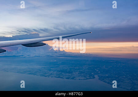 Looking from window to Air plane Wing in Flight , with beautiful scenery of sunset sky - Stock Photo