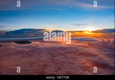 Looking from window to Air plane Wing in Flight , with beautiful scenery of amazing cloud formations on sunset sky - Stock Photo