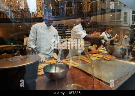 Belgium, Bruges (Brugge), employees at the Aux Merveilleux de Fred pastry shop, working at the shop display window - Stock Photo