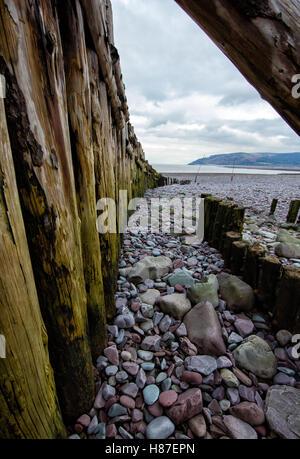 Timber groynes and shingle beach looking towards Hurlstone Point at Porlock Weir on the edge of Exmoor Somerset - Stock Photo