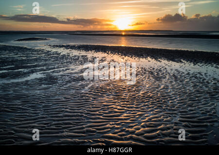 Flinthorndünen, Langeoog.  Deutschland.  Germany.  A view from the beech at low tide with the sun setting over the - Stock Photo