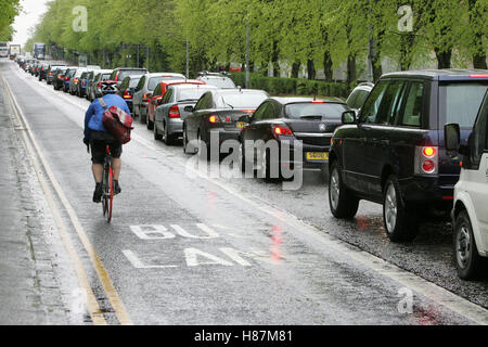 Cyclist passing traffic in rush hour - Stock Photo