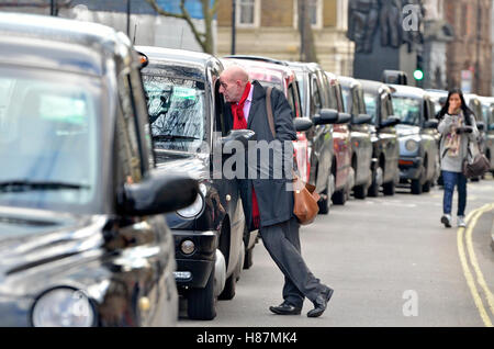 London, England, UK. Man talking to black cab driver in a long cue of taxis during a protest against Uber, Feb 2016 - Stock Photo