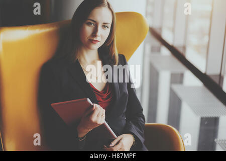 Portrait of young serious successful woman entrepreneur in a red dress and jacket sitting on yellow armchair with - Stock Photo