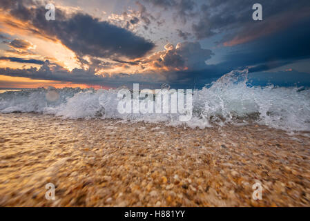 Colorful beach destination sunrise or sunset with beautiful breaking waves - Stock Photo