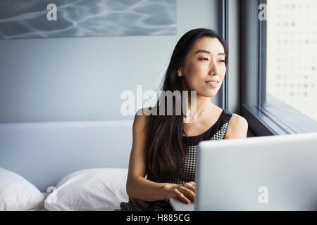 A business woman dressed, sitting on her bed using a laptop. - Stock Photo