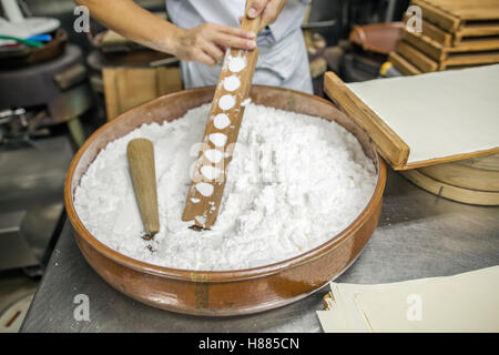 A small artisan producer of wagashi pressing the mixed dough into moulds in a commercial kitchen. - Stock Photo