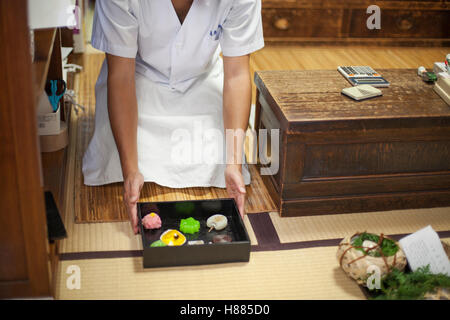 A small artisan producer of wagashi presenting a tray of selected wagashi of different shapes and flavours. - Stock Photo