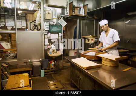 A small artisan producer of wagashi. A man mixing a large bowl of ingredients and pressing the mixed dough into - Stock Photo