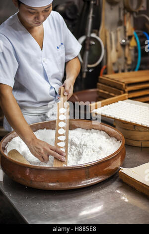 A small artisan producer of wagashi, pressing the mixed dough into moulds in a commercial kitchen. - Stock Photo