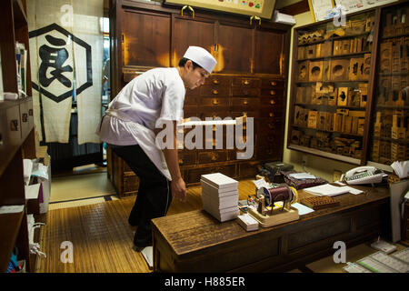 A small artisan producer of specialist treats, sweets called wagashi. A man holding a tray. - Stock Photo