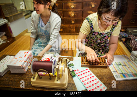A small artisan producer of specialist treats, sweets called wagashi. Two women working packing sweet boxes for - Stock Photo