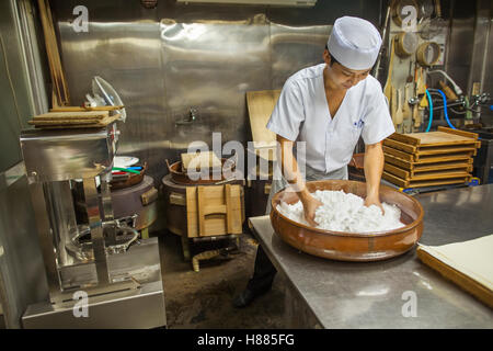 A small artisan producer of wagashi. A man mixing a large bowl of ingredients - Stock Photo