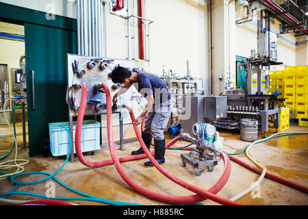 Man working in a brewery, connecting hoses to a metal beer tank. - Stock Photo