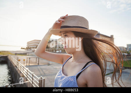 Young woman standing on a pier by water holding her straw hat on her head. - Stock Photo