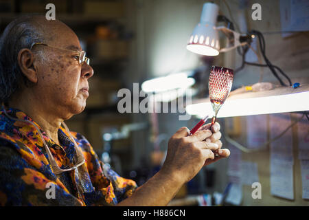 glass maker's studio workshop, man inspecting red wine glass with cut glass decoration against the light. - Stock Photo