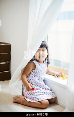 Family home. A girl playing by a window, hiding behind the net curtain. - Stock Photo