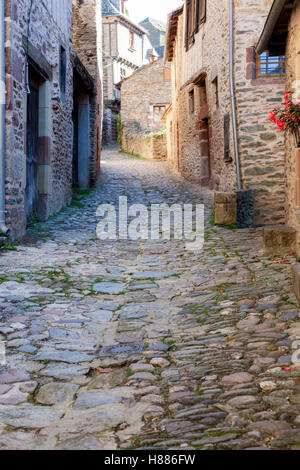 A cobbled alleyway in Conques (France). That medieval village shows tourists its abbey-church and houses topped - Stock Photo