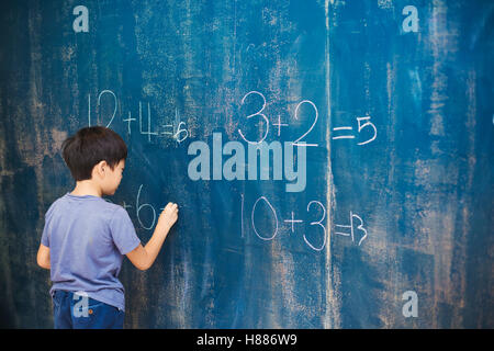 A group of children in school. A boy writing in chalk on a chalkboard. doing sums, calculating - Stock Photo