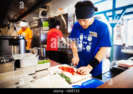 The ramen noodle shop. Three chefs working in a small kitchen, staff preparing food - Stock Photo