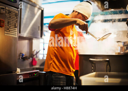 The ramen noodle shop. Staff preparing food in a steam filled kitchen. - Stock Photo