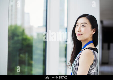 A business woman by a window with a view over the city, - Stock Photo