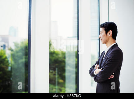 A businessman in the office, by a large window, looking out. - Stock Photo