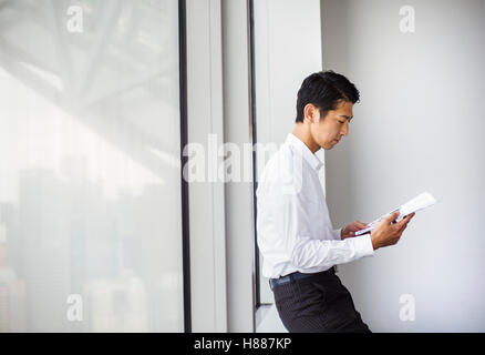 A businessman in the office, by a large window reading paperwork. leaning against the window sill. City office. - Stock Photo