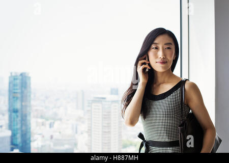 A business woman by a window with a view over the city, using her smart phone. - Stock Photo