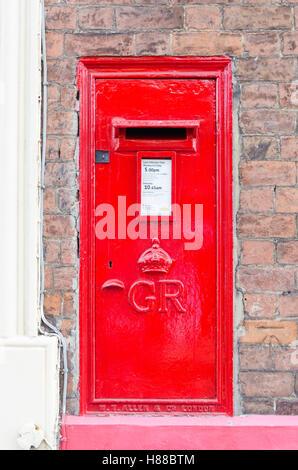 Bright red Royal Mail post box mounted into brick wall - Stock Photo