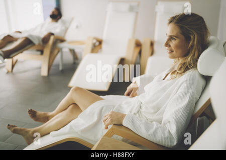 Beautiful woman relaxing in bathrobe in spa center - Stock Photo