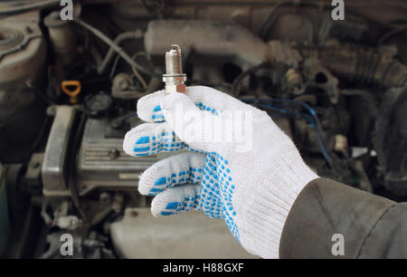 A new spark plug in hand - Stock Photo