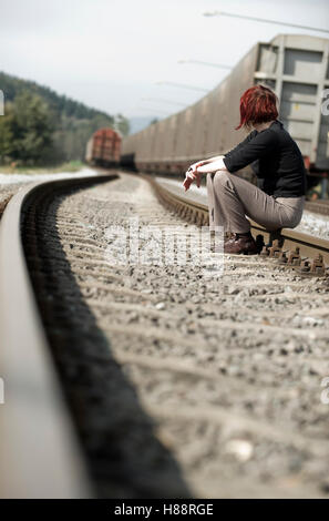Young woman sitting on a railway track - Stock Photo