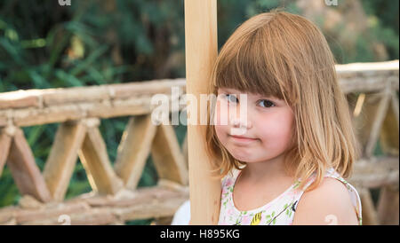 Cute Caucasian little girl standing on balcony, close-up outdoor portrait - Stock Photo