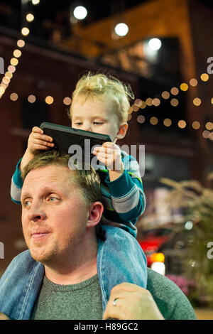 Detroit, Michigan - Two-year-old Adam Hjermstad Jr. looks at a cell phone while riding on the shoulders of his dad. - Stock Photo