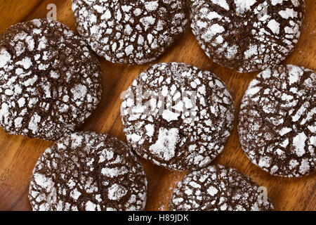 Chocolate crinkle cookies, traditional American Christmas cookies, photographed overhead on wooden plate with natural - Stock Photo