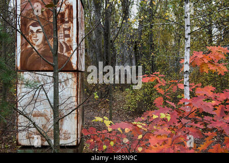 A leftover advertising pillar from the Soviets amid the abandoned, overgrown city of Pripyat. Chernobyl Exclusion - Stock Photo