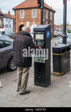 An elderly man buying a street parking ticket from a machine Yarm Stockton on Tees England UK