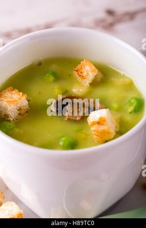 Vertical photo with detail of split pea soup. Green food in small white coffee cup with few bread croutons, peas - Stock Photo
