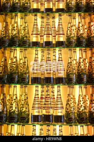 Vancouver, BC, Canada - July 26, 2010: Rows of Evian and Badoit mineral water bottles on backlit shelf. Both drinks - Stock Photo