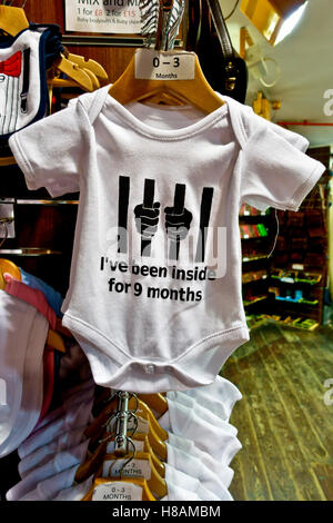 """White baby bodysuit hanging in a shop, reading """" I've been inside for  9 months"""" - Stock Photo"""