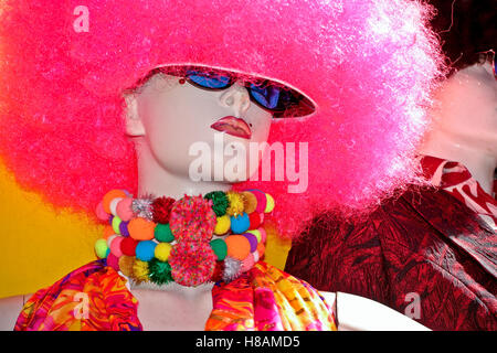 Female mannequin with fake pink wig, synthetic curly hair, sunglasses, colored necklace - Stock Photo