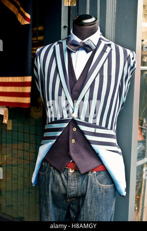 man pale blue and  black stripes jacket, white shirt, bow tie, waistcoat,  jeans on a mannequin, outside a shop - Stock Photo