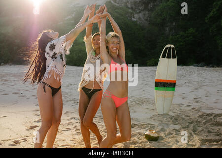 Happy female friends partying on the beach and dancing. Women having fun on the beach party. - Stock Photo
